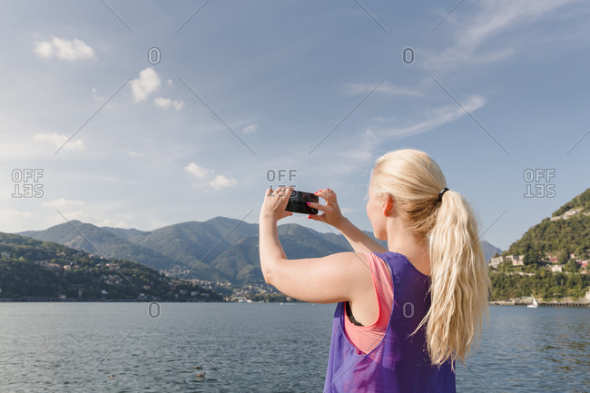 Female tourist photographing lake, Como, Italy