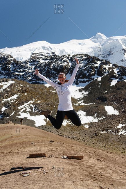 Young woman leaping, Ausangate, Willkanuta mountain range, Andes, Peru