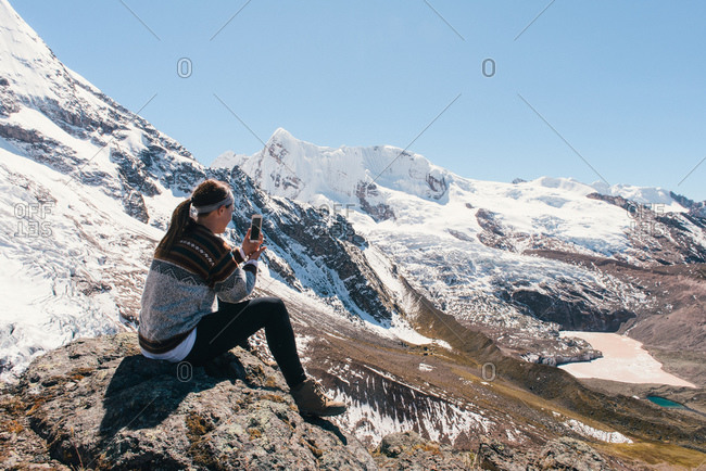 Young woman using camera phone, Ausangate, Willkanuta mountain range, Andes, Peru