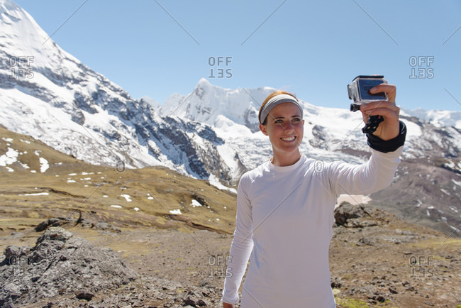 Young woman photographing herself, Ausangate, Willkanuta mountain range, Andes, Peru