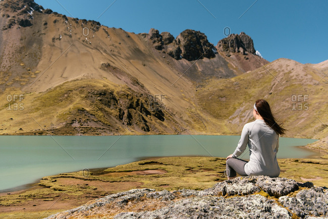 Young woman sitting by lake, Ausangate, Willkanuta mountain range, Andes, Peru