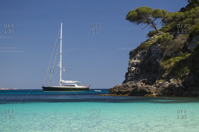 Coastal view with yacht on horizon, Cala Macarelleta, Menorca, Spain