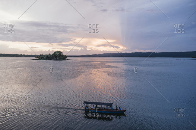 Water taxi on lake at sunset, Flores, Guatemala, Central America
