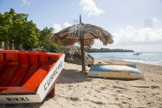 January 14, 2015: Beach umbrella and boats, Westpunt, Curacao, Caribbean