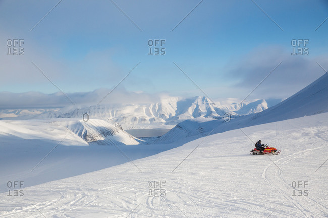 Distant view of person on snowmobile in landscape, Svalbard, Norway