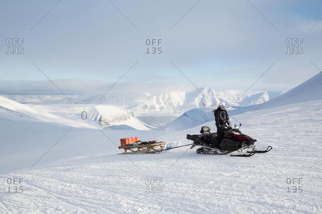Snowmobile pulling sleigh in landscape, Svalbard, Norway