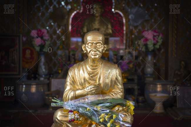 Golden buddha statue adorned with flowers
