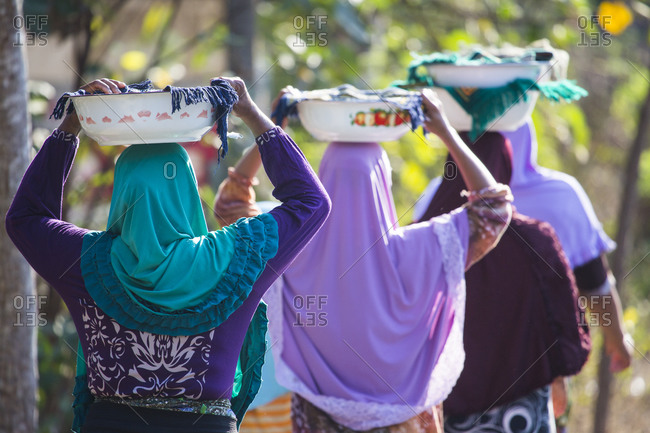 Rear view of Muslim women carrying religious offerings on their heads, Lombok, Indonesia