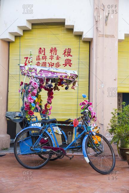October 30, 2015: Blue cycle rickshaw with garlands, Malacca, Malaysia