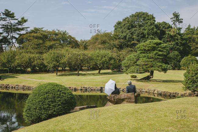Tourists by lake in Shinjuku Gyoen National Garden, Tokyo, Japan