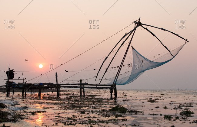 Pier and fishing nets on beach at sunset, Kochi, Kerala, India