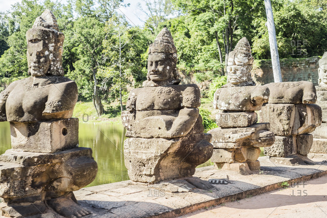 Row of lakeside statues at Phimeanakas temple, Ta Phom, Angkor Thom, Cambodia
