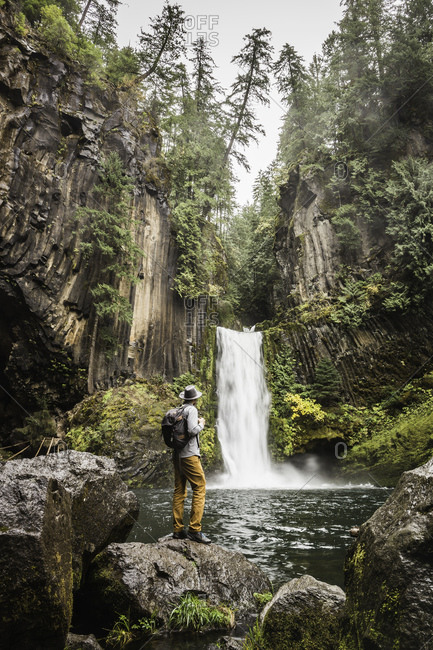 Man standing on boulder looking at Toketee Falls, Umpqua National Forest, Oregon, USA