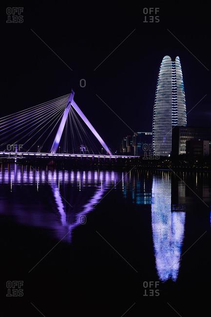 March 26, 2017: Floodlit bridge and skyscraper over river at night, Ningbo, Zhejiang, China