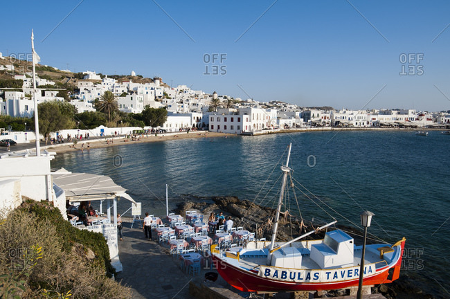 June 28, 2010: Restaurant by sea, Mykonos Town in background, Cyclades, Greece