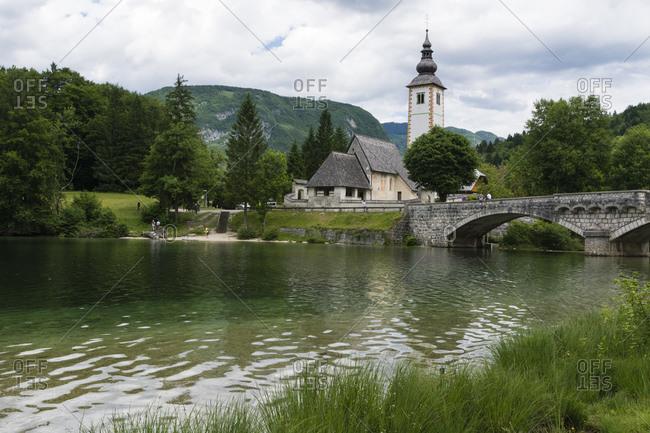 Church of St John the Baptist and the stone bridge over lake Bohinj, Slovenia