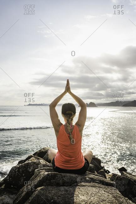 Tourist practicing yoga on rocks, Mawi Beach, Lombok, Indonesia
