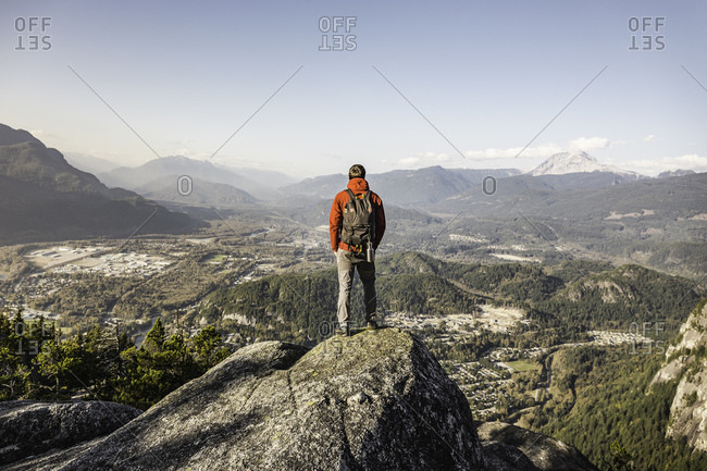 Man standing on mountain, overlooking Howe Sound Bay, Squamish, British Columbia, Canada