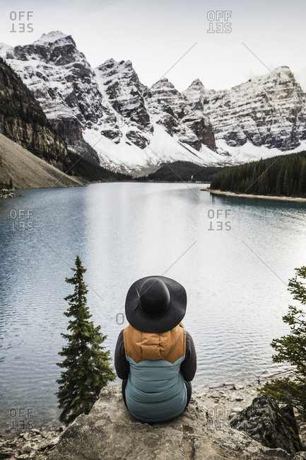 Woman sitting, looking at view, Moraine Lake, Lake Louise, Alberta, Canada