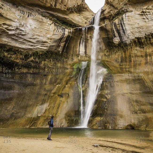 Man hiking near waterfall, Calf Creek Falls near Escalante, Utah, USA