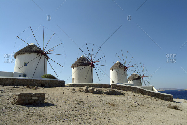 Row of traditional windmills on beach, Mykonos, Cyclades, Greece