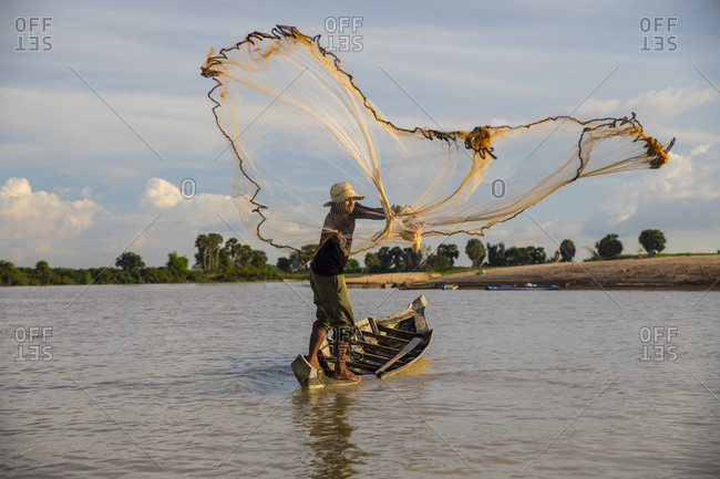 November 17, 2017: Local fisherman throwing net on Steung Saen River, Kampong Thum, Cambodia