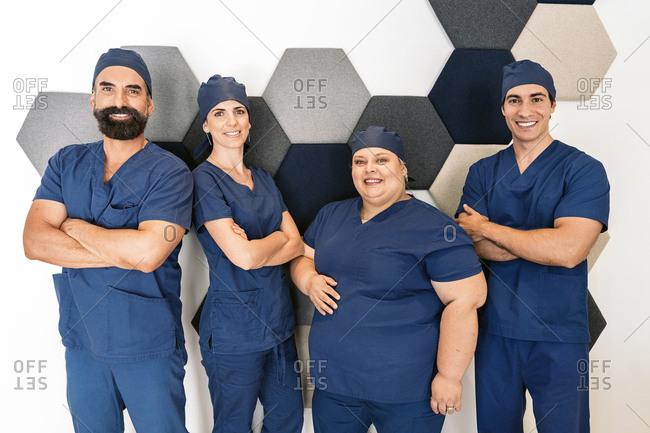 Group of dental professionals dressed in blue scrubs and caps
