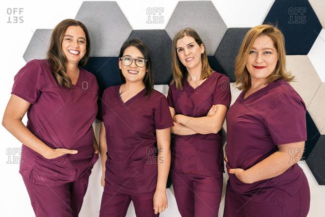 Group of dental assistants dressed in maroon scrubs
