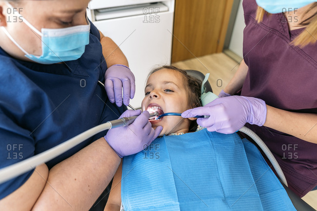 Dentists performing a filling on a young girl in a dental clinic