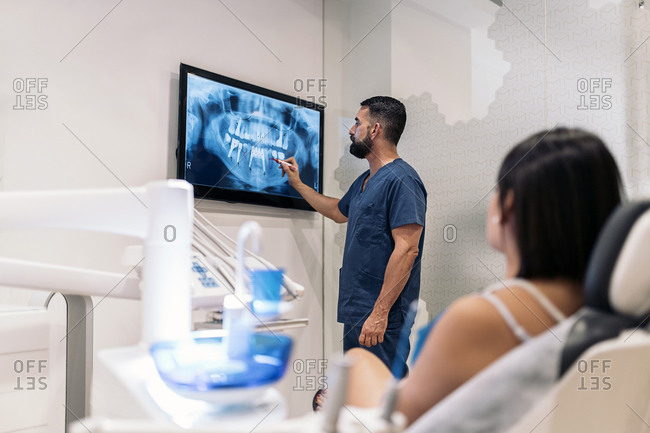 Male dentist reviewing female patient x-rays in a dental clinic