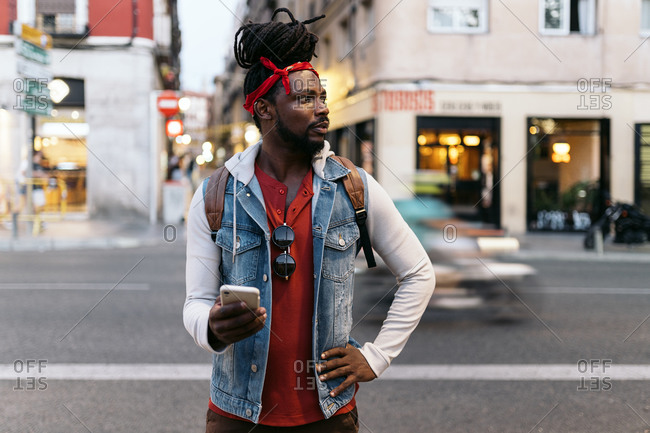 Attractive African American man with dreadlocks and a bandana walking in the street and using his phone