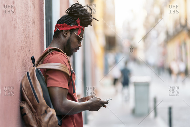 African American man with dreadlocks and a bandana walking in the street and using his phone