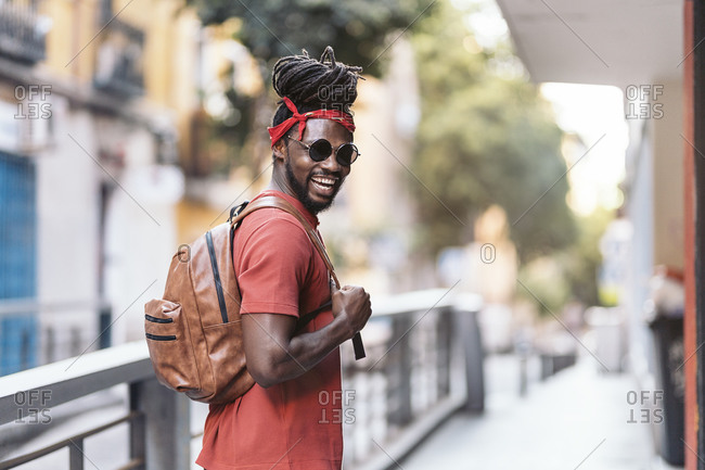 Happy African American man with dreadlocks and a bandana walking in the street