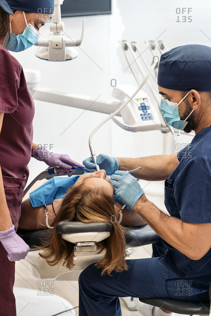 Dentist performing a procedure on a woman in a clinic