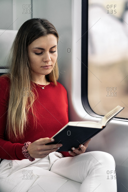 Young attractive woman reading in the train