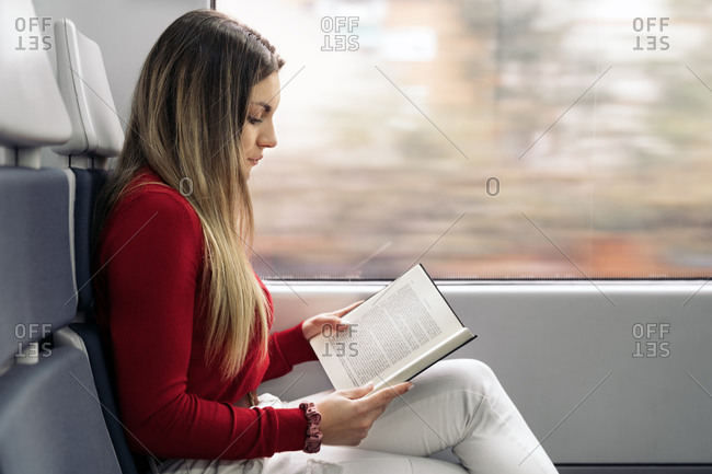 Profile view of a young attractive woman reading in the train