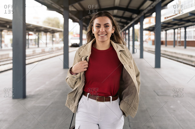Smiling woman looking at camera standing in a train platform