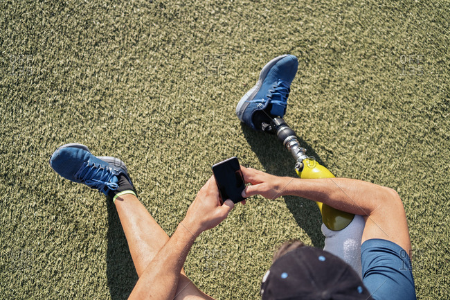 Disabled male athlete using his phone while sitting in the grass