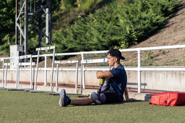 Disabled male athlete stretching with leg prosthesis