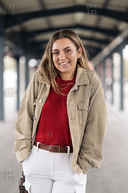 Smiling woman looking at camera standing in a train platform with her hands in her pockets