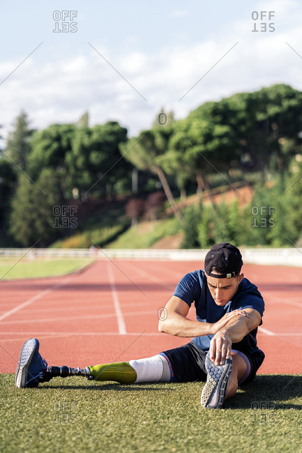 Disabled male athlete stretching his legs on grass with leg prosthesis
