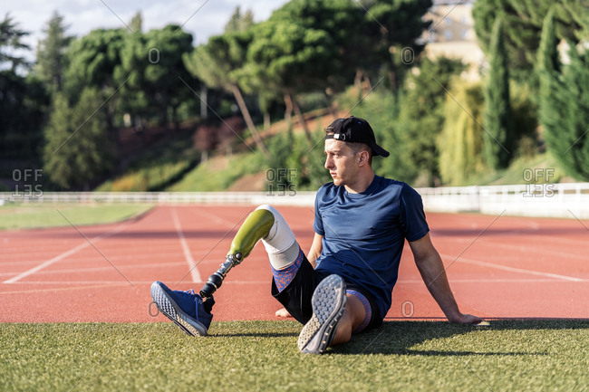 Disabled male athlete taking a break in the grass