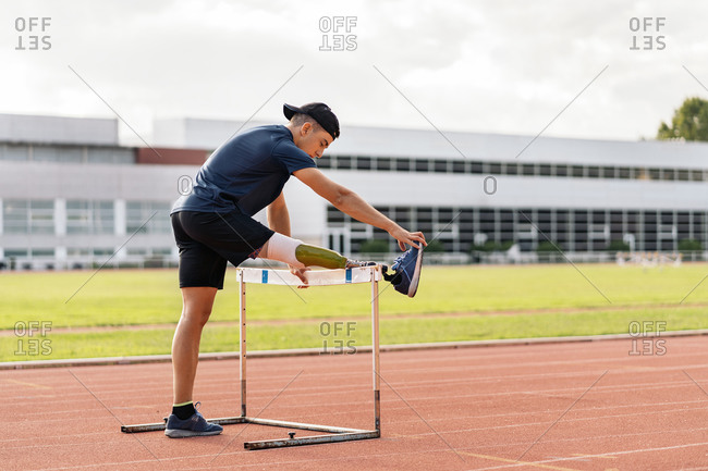Disabled male athlete stretching with leg prosthesis over a hurdle