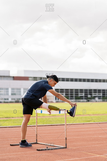 Young disabled male athlete stretching with leg prosthesis over a hurdle