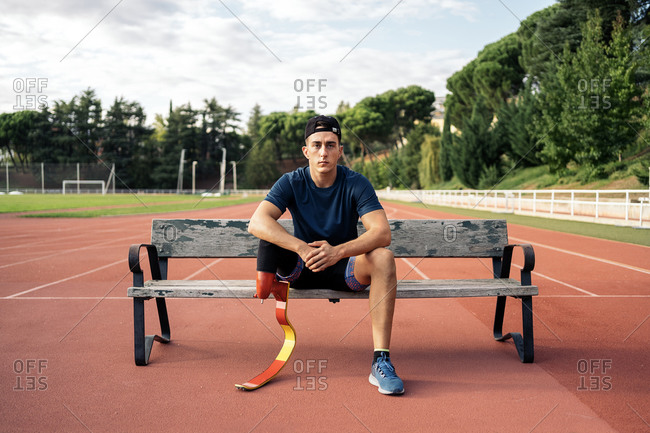 Disabled male athlete sitting in a bench and looking at camera