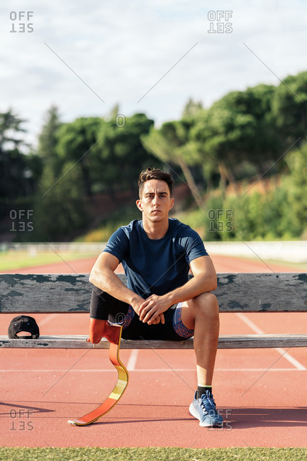 Disabled male athlete with a running prosthesis sitting in a bench and looking at camera