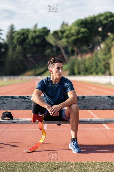 A disabled male athlete with a running prosthesis sitting in a bench and looking away