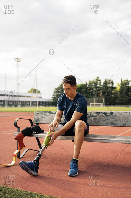 Disabled male athlete sitting in a bench and putting on his leg prosthesis