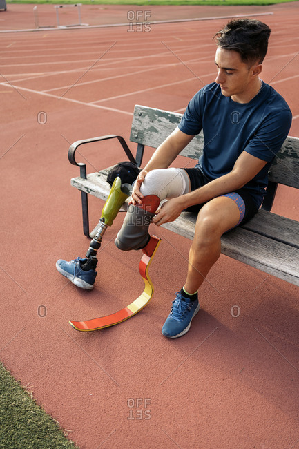 Young disabled male athlete sitting in a bench and putting on his leg prosthesis