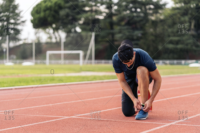 A young disabled male athlete taking a break and tying his training shoes